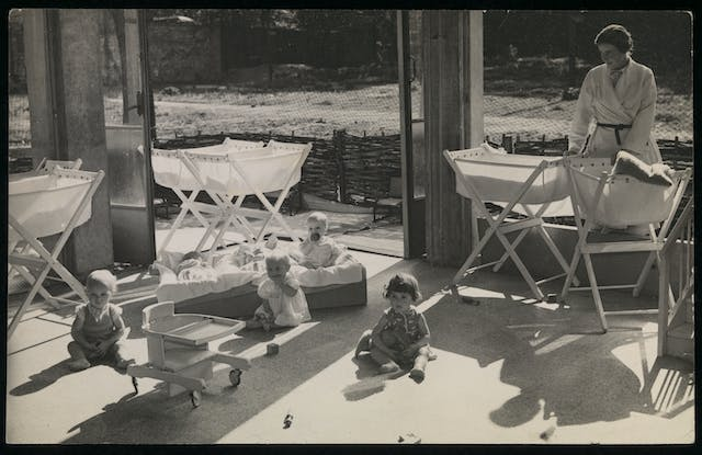 Black and white photograph showing a nursery, with several small children and a female nurse.
