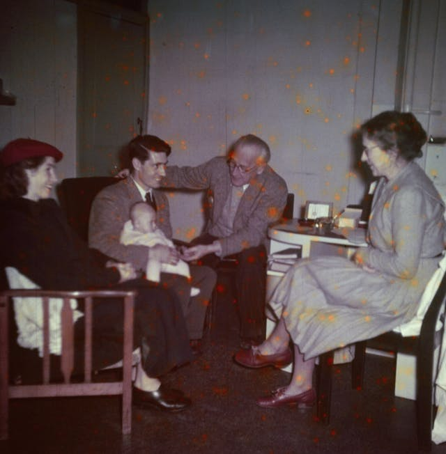 Photograph from the mid-20th Century Peckham Pioneer Centre, showing a man and woman seated on the left, the woman wearing a bright red beret and the man holding a baby on his lap. An older man reaches across towards the hand of the baby, and an older woman sits at a desk with her legs crossed, smiling at the group.