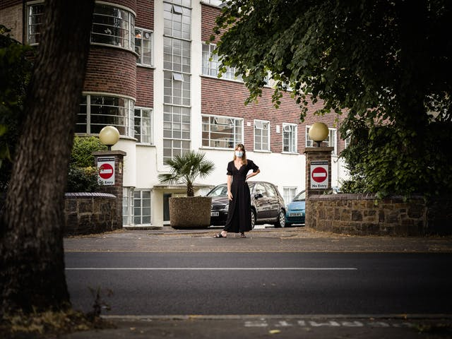 Photograph of a woman in a black dress and wearing a blue face-mask standing in the middle of an exit to a residential building. Two signs displaying the do not enter circle with white dash appear on pillars either side of the exit. The shot is captured from the other side of the road and features the trunk of a tree, the road and part of the pavement in the foreground.
