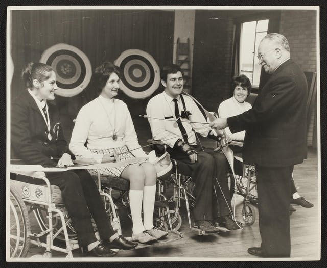 Black and white photographic print of Sir Ludwig Guttmann, on the right of the photograph, meeting with four athletes sitting in wheelchairs. Guttman wears a dark suit and shoes and faces away from the camera and toward the athletes but you can see from his profile that the bespectacled man with light hair is smiling. The athletes hold sporting equipment. The woman on the left has a beaming smile and medal and wears her hair in a bun. She holds a bow across her lap. The woman who is second from left is also smiling and has two medals around her neck. She holds a fencing foil, as does Guttmann, who appears to be speaking with her and chuckling at the moment the photograph was taken. Next is a grinning man with dark hair wearing a medal and a shirt and tie. He has straps on his wrists and holds a bow. Slightly behind Guttmann in the photograph, there is another smiling woman who also appears to have a medal ribbon around her neck.