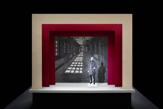 Photograph of a simple theatre stage set, made out of card. The background surrounding the stage is black. The stage floor is white and the framing of the stage is made out of 3 square edged arches, each one smaller than the other, receding backwards. The first arch is cream coloured and the other two are a red. On the stage is a small cut out illustration of a man with a beard from the early 20th century. Behind him forming the backdrop is a black and white drawing of a long corridor with windows down the left side, casting a strong shadow on the floor.