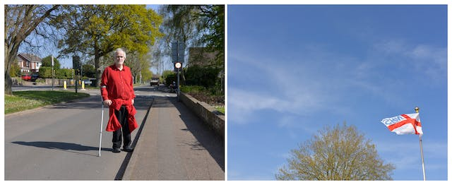 A photographic diptych. The image on the left shows a middle-aged man with grey hair wearing a red shirt and black trousers holding a crutch in his right hand. He stands in the 20 MPH zone road which has a small central reservation lined with trees.  The image on the right shows a blue sky on the bottom right of which is the St George's flag flying with NHS (from the reverse side) written in blue in the top left quarter. To the left of the flag, is the top of a large tree lightly covered in yellow green foliage.