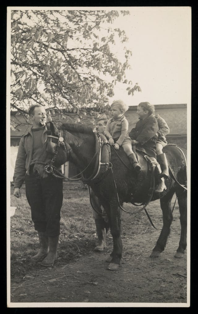 Black and white photograph showing a man leading three toddlers who are sitting on the back of a horse.