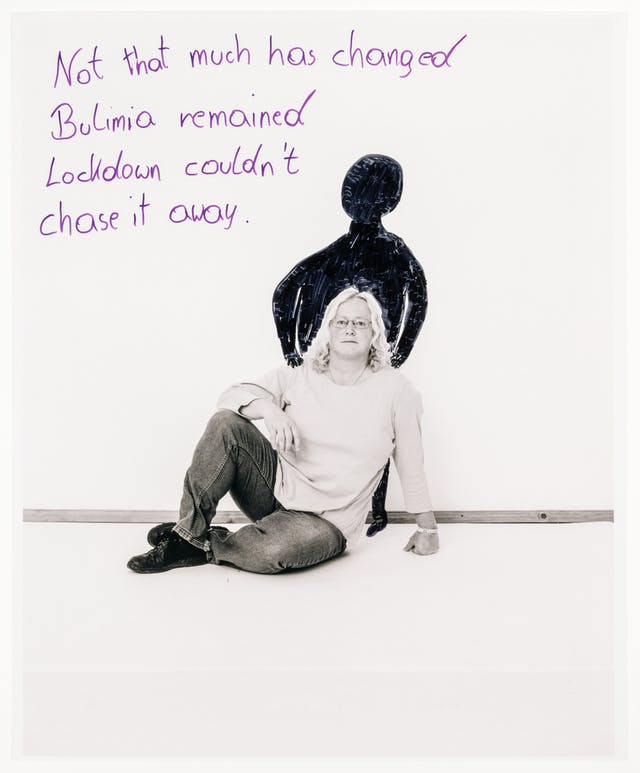 """Full body photograph of a woman sitting on the floor with her legs crossed, with one arm resting on her knee and the other supporting her body upright. Hand drawn behind her is a black figure with its hands resting on the shoulders of the woman.  Behind her, the words """"Not that much has changed, Bulimia remained, Lockdown couldn't chase it away"""" are written in purple marker."""
