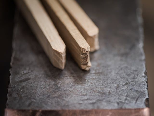Photograph of specially crafted wooden sticks resting side by side on a metal surface.  Each stick will make a different impression on solidified lead. Two of the sticks used in tandem will create a cross, and the third stick will create a line.