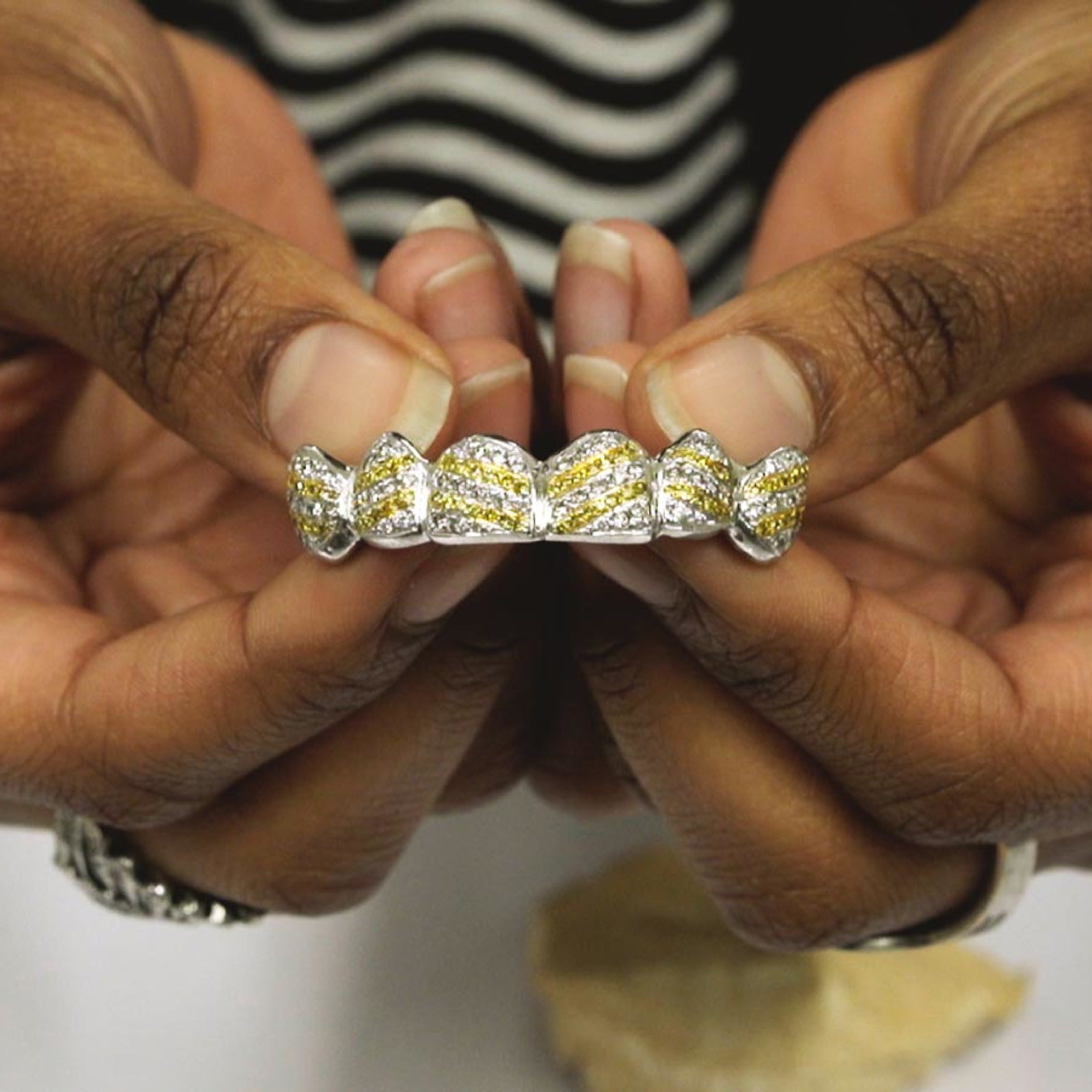 a pair of hands presenting a jewel encrusted grill for the mouth