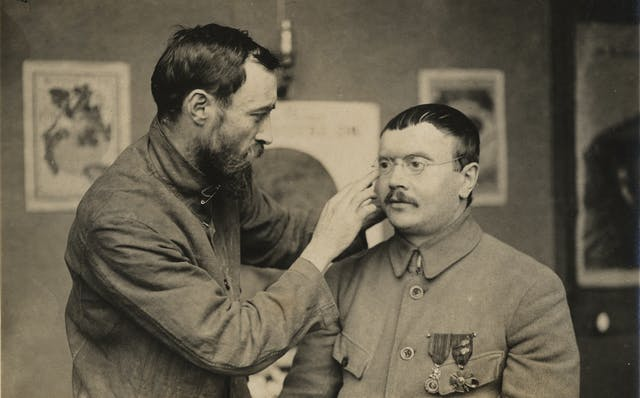 A man adjusts the spectacles on another man