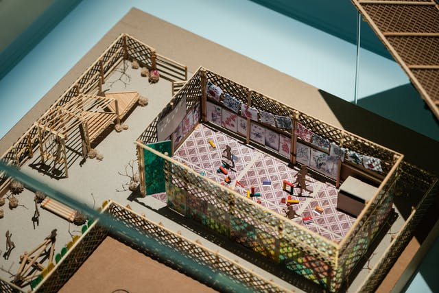 Photograph of a model of a buildings and outside spaces made in wood. Inside one of the structures are small figures representing children who are in the process of playing with colourful blocks.