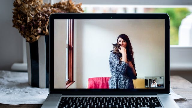 Photograph of an open laptop within a domestic scene. Most of the image is taken up with the screen, with part of the keyboard and trackpad visible. On the screen is a video call showing a woman standing in her living room, holding a cat in her arms, both are looking to camera. In the bottom right corner of the screen the photographer can be seen in a small floating window, camera to her eye, in the process of taking the picture.