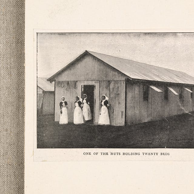 Black and white photo of a metal hut with four nurses standing outside the front. It is captioned: