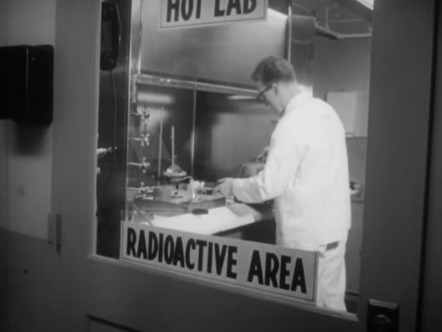 Still from black and white film featuring a doctor wearing a lab coat working. He is framed by the window of a door which has a label on it saying