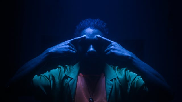 Film still of a man in a dark space, lit with a single blue light from directly above his head, casting much of his face into shadow. He is only visible from the chest up. He is wearing a green shirt, a light red t-shirt and a chain necklace. Both his arms are raise with both his index fingers pointing to his forehead, just above his eyebrows.