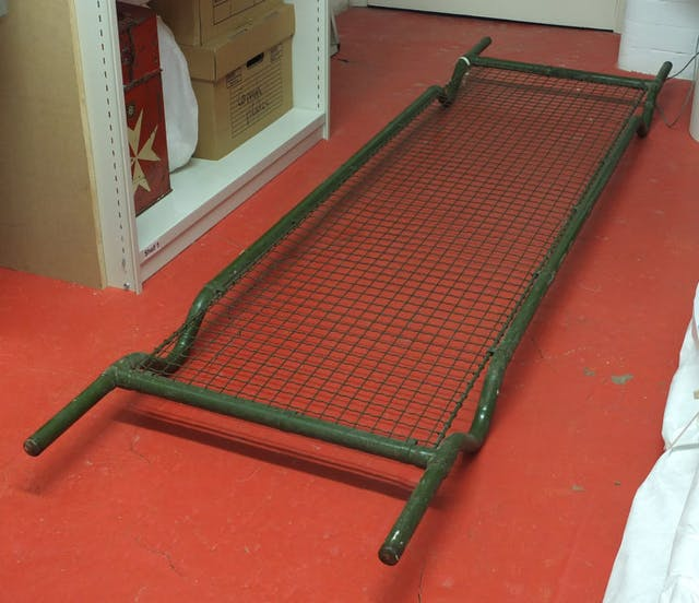 Photo of metal stretcher against red floor
