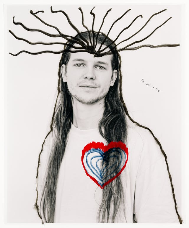 """Head and shoulders photograph of a man with long hair staring at the viewer.  His body has been outlined with a black marker pen; hand drawn on the photograph.  A series of lines emanate from the man's head.  A blue and red heart shape has been drawn on his chest.  In small handwriting, the words """"I'm just so tired"""" have been written to the left of his portrait."""