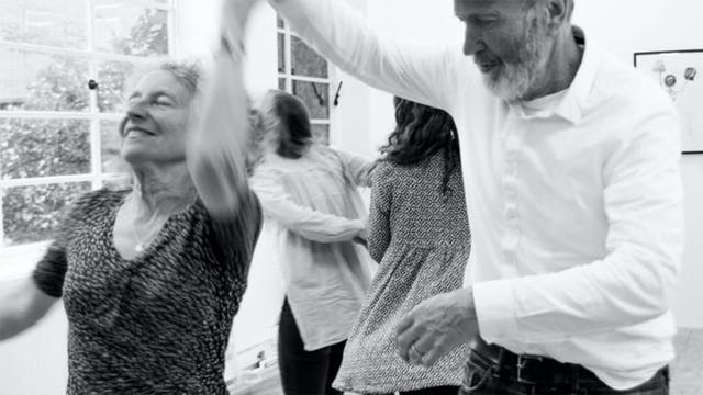 A black and white of photograph of an older man and woman dancing.