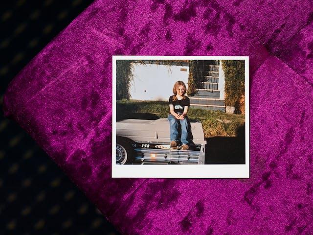 一个年轻女孩的家庭照片的印刷品的照片外面的,坐汽车拖车的上面。她穿着牛仔裤和一件黑色的T恤,对镜头微笑。她身后是一个草地,旁边的道路和前白色花园墙,门和房子的台阶。印刷品躺在紫色天鹅绒面料的顶部,这是遮荫的一部分,部分在阳光下。