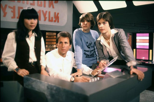 Four young people clustered around a futuristic control desk behind which there is alien lettering.