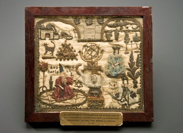 Image of embroidered square with wooden frame.