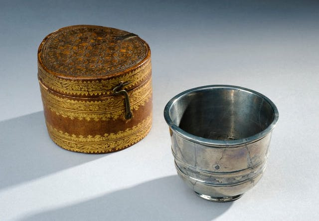 Image of small silver metal cup with an ornate leather case next to it.