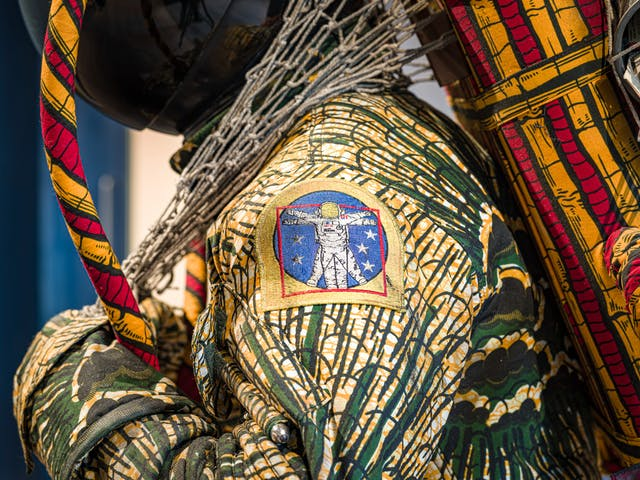 Photograph of a close-up detail of the shoulder of a life-size artwork of a figure resembling an astronaut, carrying a large net containing assorted objects. On the shoulder is an embroidered badge showing an astronaut with arms and legs outstretched within a blue circle.