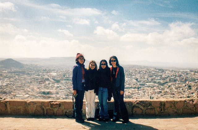 Photograph of a group of four young women standing by a low wall, behind which a vista of Mexico City extends into the distance.