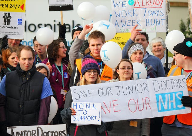 "Colour photograph of a group of people on strike. They wear coats, gloves and hats, and some wear high-visibility jackets that have ""BMA"" printed on them. Placards and banners include ""We already work 7 days a week Hunt"" and ""Save our junior doctors. Save our NHS."""