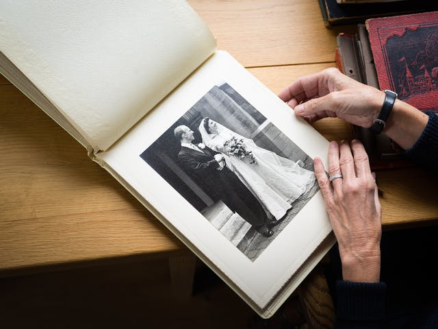 A photograph of an open photo album with a large photo of a man and a woman on their wedding day. A pair of hands lay across the bottom right of the wedding photo and on the left hand there is a silver ring. The album is on a wooden desk and to the right are piles of other photo albums.