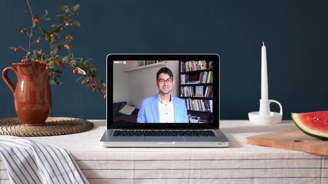 Photo of a laptop with a video chat image of a man in a blue blazer. On the table are a jug with foliage, a candle and a watermelon on a chopping board