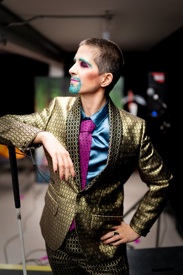 Photograph showing a performer backstage. The performer is dressed in a shiny gold suit. Their right elbow is resting on the handle end of a white cane. Their left hand is resting on their hip. Their mouth and eye brows are covered in blue glitter make-up.