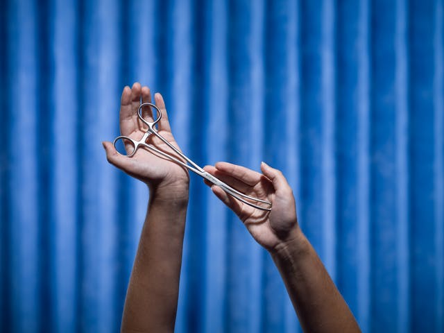Photograph of a pair of hands cradling a set of forceps. Photographed against a background of blue antibacterial clinical curtains.
