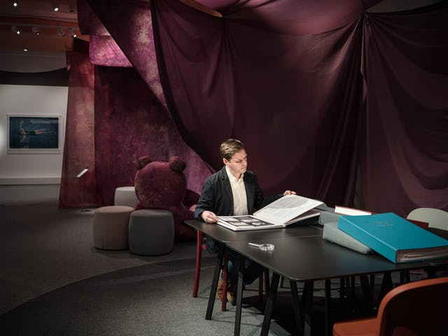 Photograph of a man sitting at a black table on a red chair leafing through a large photo book and reading the text.  In the background there is the