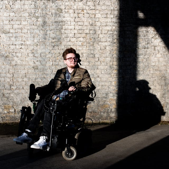 Photograph of a young person in a motorised wheelchair outside, in front of a white washed brick wall. They are lit by a low sun which is casting long shadows against the wall.