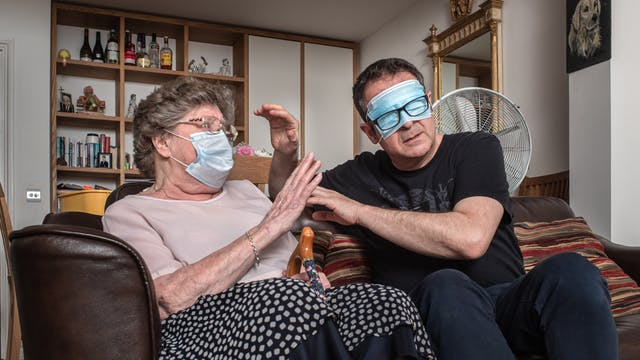 Photograph of a man and his mother sat side by side on a sofa in a living room. The man seated on the right has a medial face mask covering his eyes and is wearing his black rimmed glasses over the top of the mask. He is raising his hands towards his mother as if to try to touch and feel her face. His mother is also wearing a medical face mask but over her mouth and nose and is raising her hand in defence. Rested between her legs is the handle and top half of her walking stick. In the background is a shelving unit containing books, ornaments, bottle of spirits and family photographs. On the walls are hung an ornate gilt framed mirror and a portrait painting of a dog