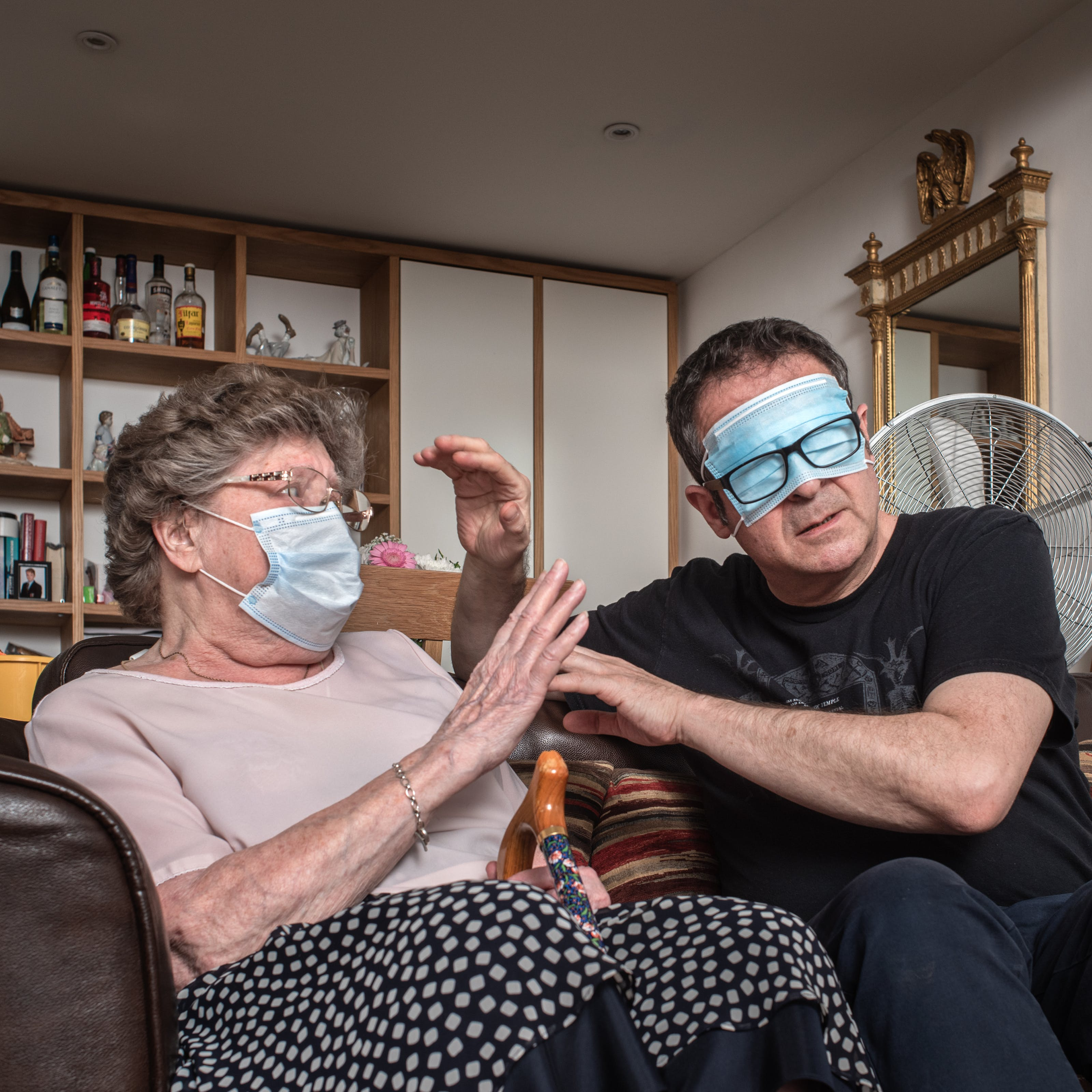 Photograph of a man and his mother sat side by side on a sofa in a living room. The man seated on the right has a medial face mask covering his eyes and is wearing his black rimmed glasses over the top of the mask. He is raising his hands towards his mother as if to try to touch and feel her face. His mother is also wearing a medical face mask but over her mouth and nose and is raising her hand in defence. Rested between her legs is the handle and top half of her walking stick. In the background is a shelving unit containing books, ornaments, bottle of spirits and family photographs. On the walls are hung an ornate gilt framed mirror and a portrait painting of a dog's head.