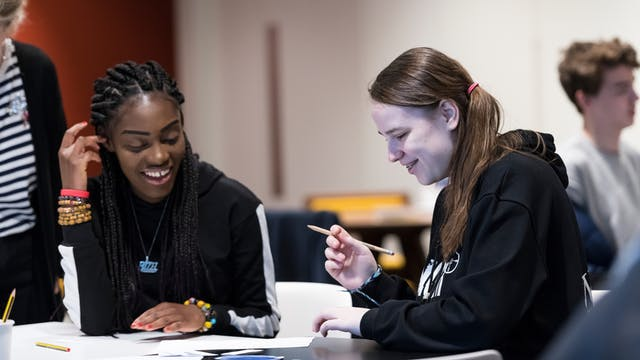 Photograph of two students sat at a table looking down at the activities that they