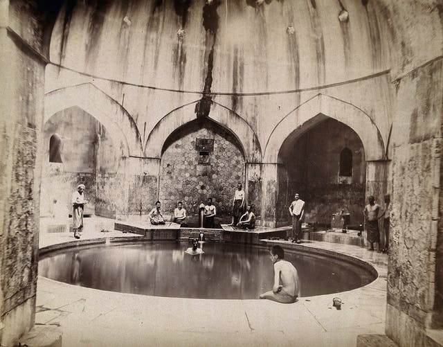 Black and white photograph showing men sitting around the sides of a circular pool in a domed building.