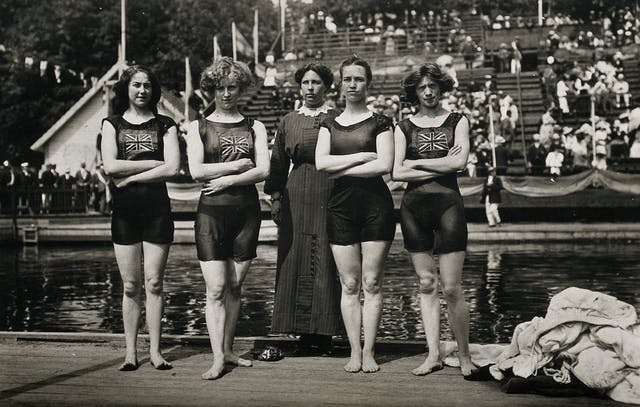 Black and white photograph of four young women wearing swimming costumes with Union Jacks posing with an older woman, perhaps their coach who is wearing an ankle-length dress with lace collar.