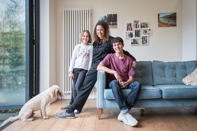 Photograph of a mother and her two children in their living room. They are sat on the sofa and the mother is in the middle, her arm around each one. In the background are family photos in frames hung on the wall. At the family