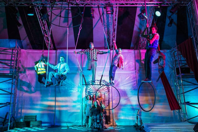 A wide angle photograph of a theatrical production lit with blue and purple lighting. A group of five performers are standing on bars and hoops suspended from the ceiling. The performer standing on the central 'trapeze' has his arms outstretched, holding the ropes. His right trouser leg is hemmed just above the knee revealing that he does not have a right leg. To the centre-bottom of the frame a further group of three performers are standing over the shoulders of a performer seated in a wheelchair.