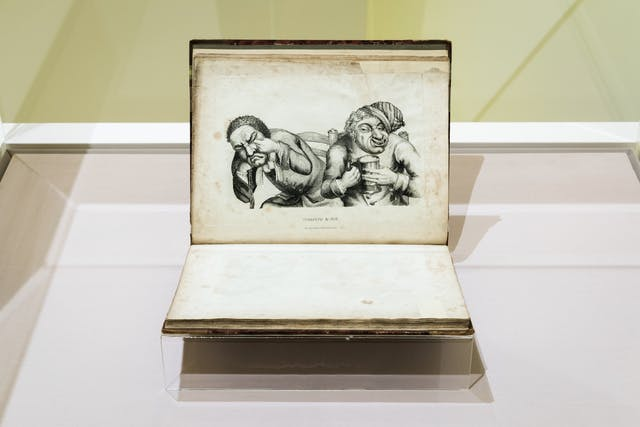 Photograph of a glass exhibition display case showing an open printed book, held in a book cradle. The book is in landscape orientation and on the upper page is an etching of two characters, one crying and rubbing their eyes and the other holding a flagon of beer and smiling.