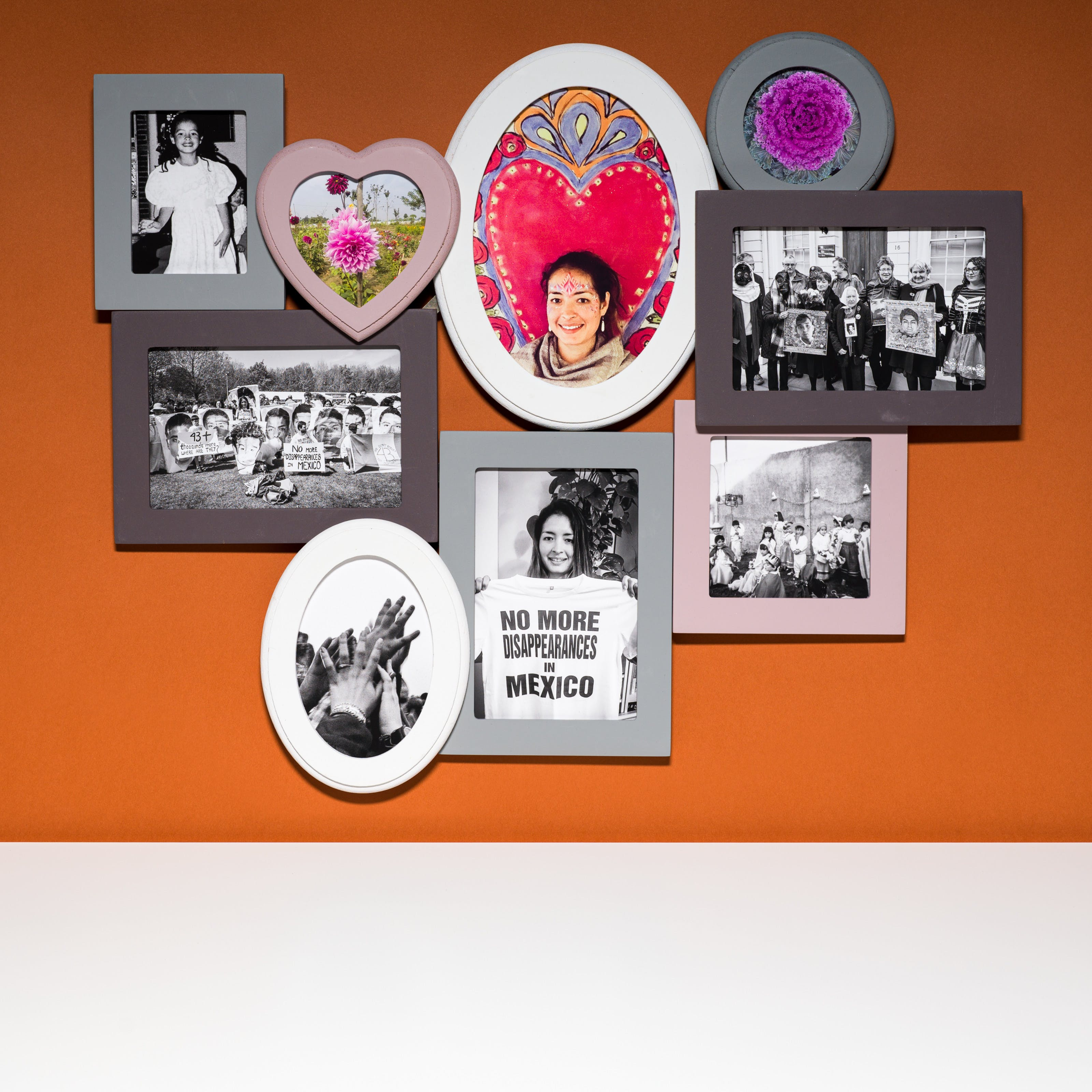 Photograph of a multiframe photo frame containing nine photographs, three in colour and six in black and white. The frame is hung on a brown wall above a white tabletop.