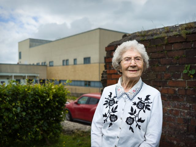 Photographic portrait of Joyce Thompson standing in front of the Royal Blackburn Hospital.