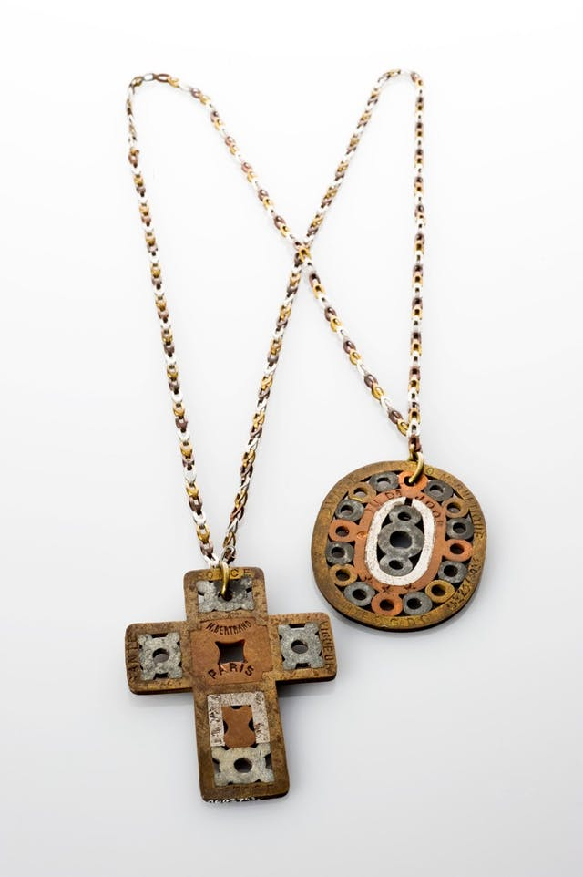 Image of a necklace with a cross-shaped and an oval-shaped amulet