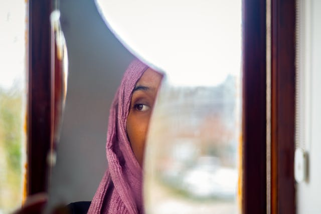 Photograph of a woman wearing a pink head scarf. We see a fragment of her face reflected in a shard of mirror. behind the mirror is a window and the view of the out of focus outside.