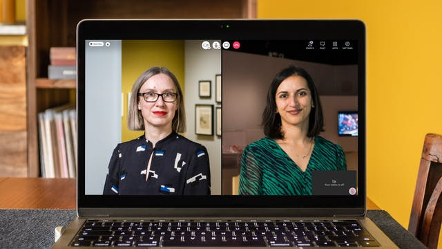 Photographic portrait of Emily Sargent and Shamita  Sharmacharja appearing on a video call on a laptop.  Emily is wearing glasses with blonde shoulder-length hair and Shamita is wearing a green striped dress with brown shoulder-length hair. The laptop is on a wooden table,  a chair and bookshelves are nearby against a yellow wall.