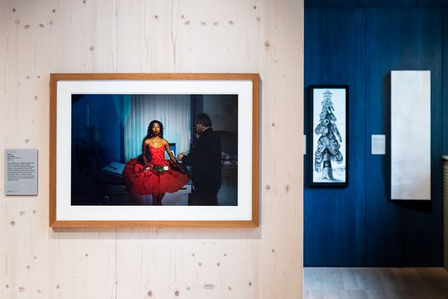 Photograph of a gallery wall showing a framed photograph of a woman in bright red dress in a medical clinic.