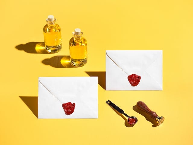 Photograph of 2 specimen bottles containing yellow liquid, 2 enveloped sealed with a red wax seal of a tree and is roots, a silver spoon and a wooden handled stamp. The whole scene has been photographed against a bright solid yellow background.