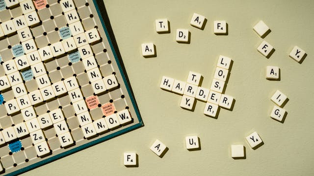 Photograph of a scrabble board filled with high scoring words to the left of the frame.  In the centre there are several words interlaced with each other that read