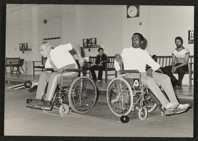 Black and white photograph showing two men playing wheelchair skittles. On the left, a white man leans down, gripping his wheelchair for balance using his left arm and reaching forward with a black skittle in his right hand, about to throw it. To his right sits a black man with his wheelchair pointing away from the throwing man, who is leaning around in his chair to watch. Behind are benches for spectators, one of whom is a bearded man in a Dallas Cowboys shirt holding a cigarette, and the other of which is a teenage boy in a dark tracksuit with white stripes running down the sleeves and front. A scoreboard in the background appears to indicate the score is 19:16.