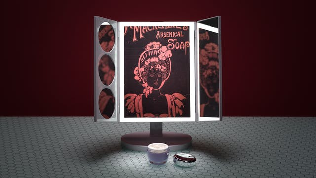 Photograph of a three-fold table beauty mirror with built-in light on a glass patterned tabletop, against a dark red background. On the table in front of the mirror is an open jar of face cream. In the reflections of the mirror an old advertisement for Dr. Mackenzie